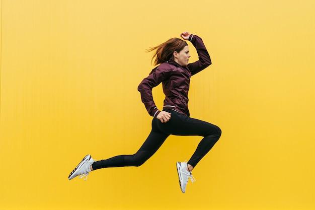 노란색 벽으로 점프하는 젊은 sportswoman