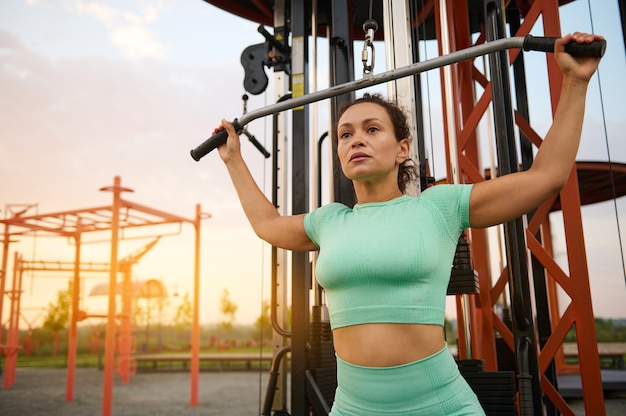 若いスポーツウーマンは、クロスオーバーストリートシミュレーターで背中の筋肉をポンピングします。日の出の屋外のジム設備で運動する混血の女性アスリート