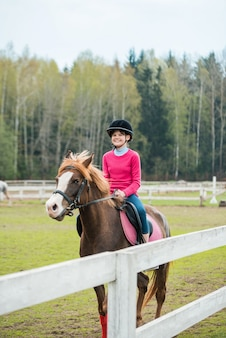 Young sportswoman riding horse in equestrian show jumps competition. teenage girl ride a horse