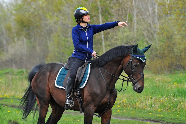 Young sportswoman riding horse