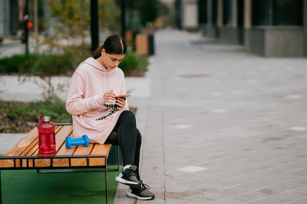 Young sportswoman sitting on the bench at the park