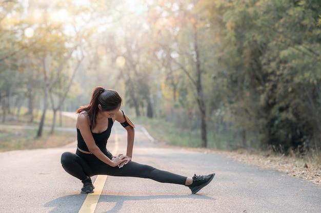 Молодая спортсменка растяжения и подготовки к бегу на открытом воздухе.