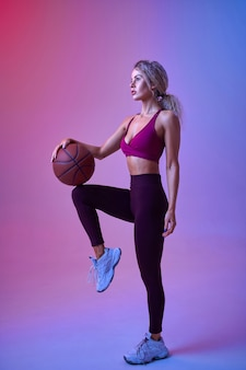 Young sportswoman with ball poses in studio, neon background. fitness woman at the photo shoot, sport concept, active lifestyle