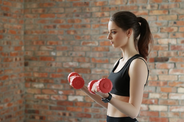 Young sportswoman with dumbbells