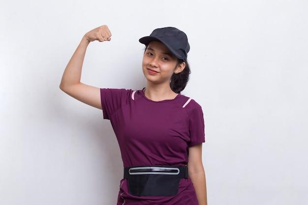 Молодой спортивный азиатский красивый показывая сильный жест на белом фоне