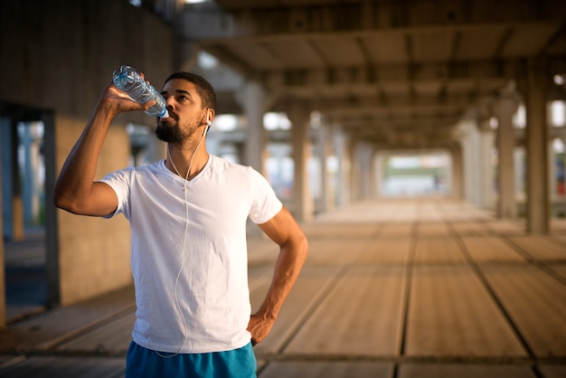 Young sporty athlete drinking water after hard training