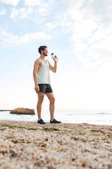 Young sporty athlete resting after jogging at the beach and drinking water