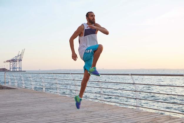 Giovane uomo di salto barbuto attraente sportivo facendo esercizi mattutini in riva al mare, riscaldamento prima di correre.