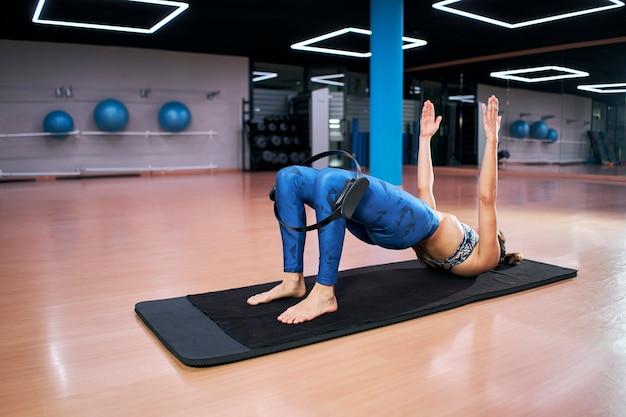 Молодая спортивная привлекательная женщина делает пилатес, тонизирующее упражнение для ног с кольцом, фитнес с волшебным кругом пилатеса на коленях, тренировка.