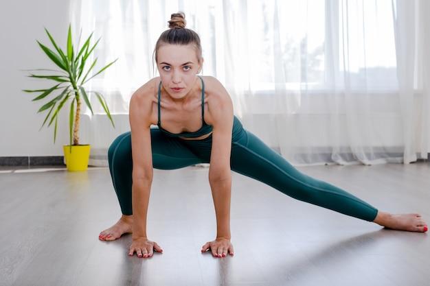戦士iii運動virabhadrasanaポーズworkinを行うヨガを練習している若いスポーティな魅力的な女性...