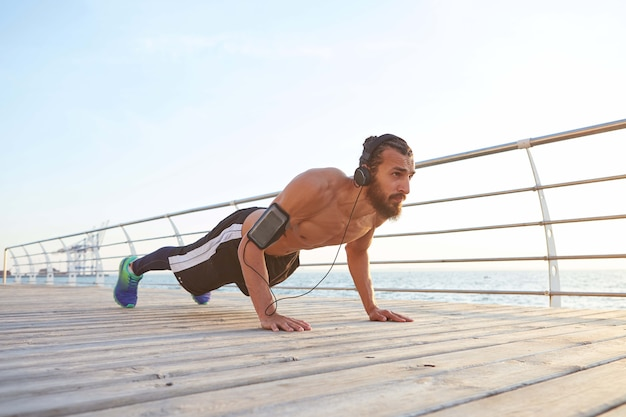 Young sporty bearded guy doing morning exercises by the sea, warm-up after run, doing pushups, keeps the plank, listening favorite songs on headphones, leads healthy active lifestyle.