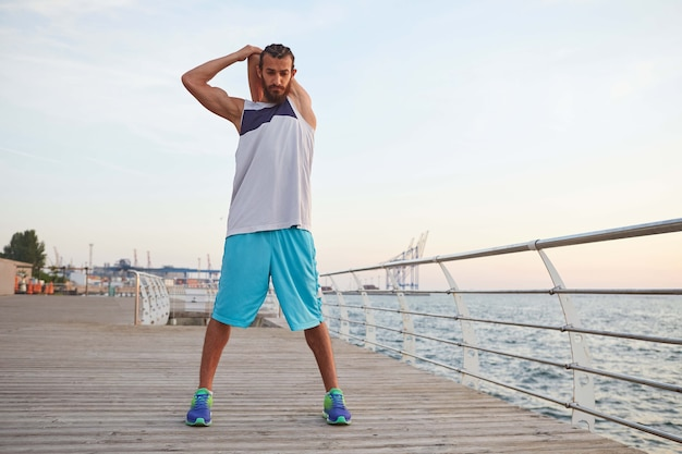 Young sporty bearded guy doing a warm-up after a morning run at the seaside, looks away.