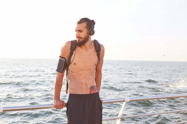 Giovane ragazzo barbuto sportivo, riposa dopo lo yoga mattutino al mare, ascolta il tuo mix preferito in cuffia.