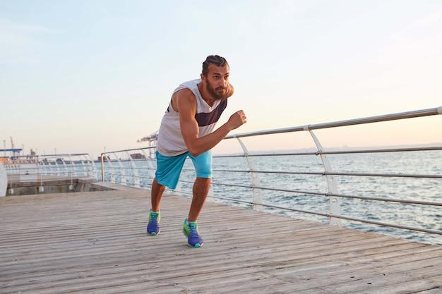 海辺で走っている若いスポーティーなひげを生やした男は、健康的なアクティブなライフスタイルをリードし、よさそうだ。フィットネス男性モデル。健康とスポーツのコンセプト。