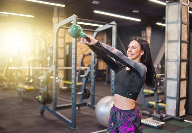 Молодая спортивная брюнетка делает рывок упражнения с гирями. в тренажерном зале. силовые тренировки со свободными весами, функциональные тренировки