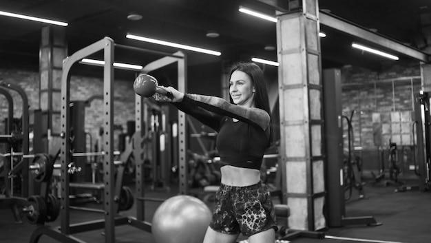 ケトルベルでジャーク運動をしている若いスポーティーなブルネット。体育館で。フリーウェイト筋力トレーニング、ファンクショナルトレーニング