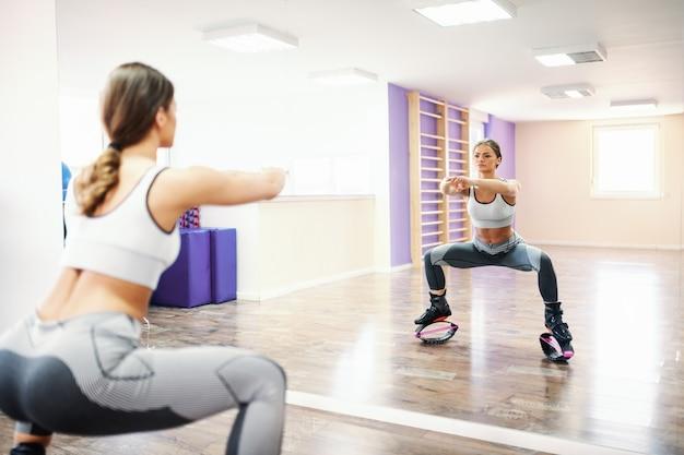 Молодая спортивная брюнетка с хвостиком и в спортивной одежде делает квадратную выносливость в kangoo прыжки обувь перед зеркалом
