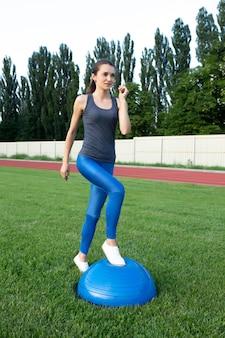 Молодая спортивная брюнетка тренируется с мячом босу на стадионе