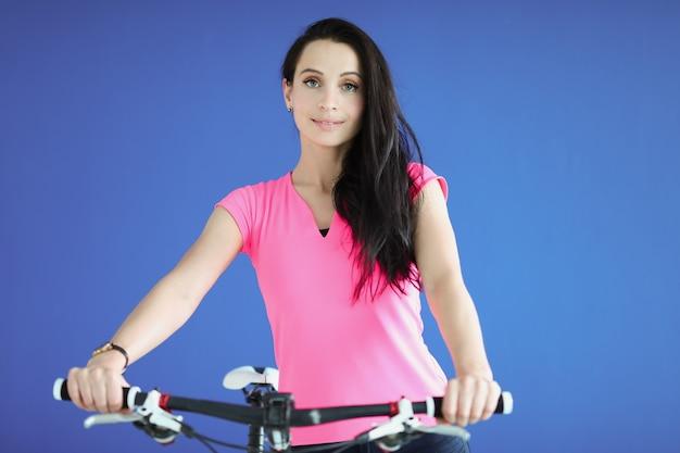 Молодая спортивная брюнетка женщина с велосипедом крупным планом