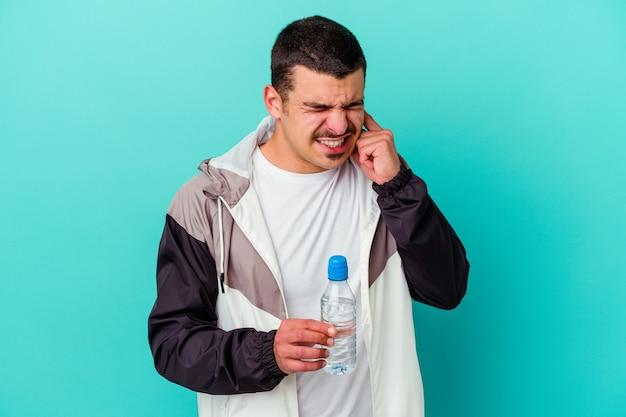 손으로 귀를 덮고 파란색에 고립 된 젊은 스포티 한 백인 남자 식 수.