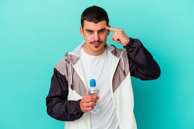 若いスポーティな白人男性が指で青いポインティング寺院に隔離された水を飲んで、考えて、タスクに焦点を当てた。