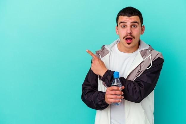 側面を指している青に分離された若いスポーティな白人男性の飲料水