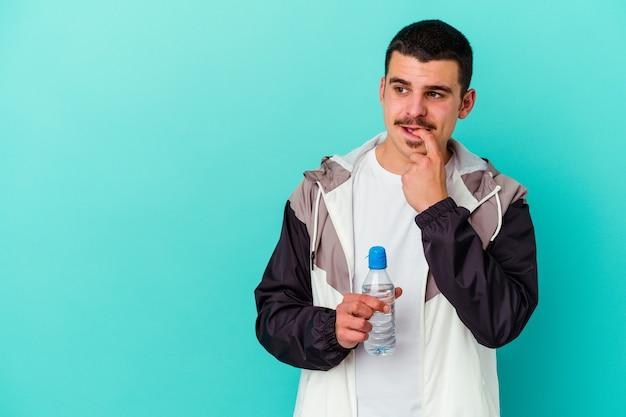 青で隔離された水を飲む若いスポーティーな白人男性は、コピースペースを見ている何かについて考えてリラックスしました。