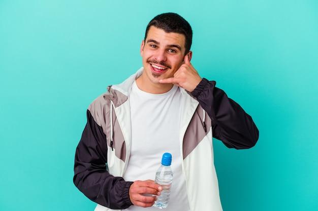 指で携帯電話の呼び出しジェスチャーを示す青で隔離の水を飲む若いスポーティな白人男性。