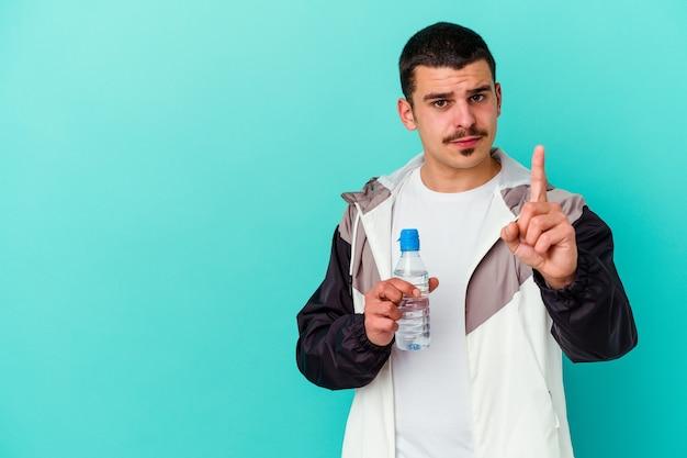 青で隔離の若いスポーティな白人男性の飲料水は指でナンバーワンを示しています。
