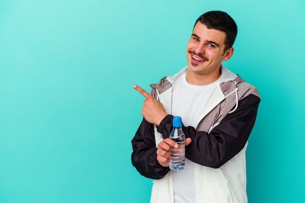 青い壁に隔離された水を飲む若いスポーティな白人男性は、笑顔で脇を指して、空白のスペースで何かを示しています。