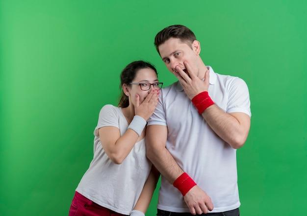 스포티 한 젊은 부부 남자와 여자 손으로 입을 덮고 녹색 벽 위에 서 충격을 받고