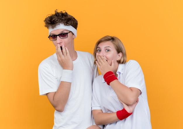 オレンジ色の壁の上に立ってショックを受けている手で口を覆っている若いスポーティなカップルの男性と女性