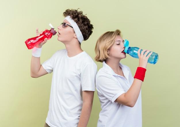 Молодая спортивная пара мужчина и женщина пьют воду после тренировки, стоя над светлой стеной