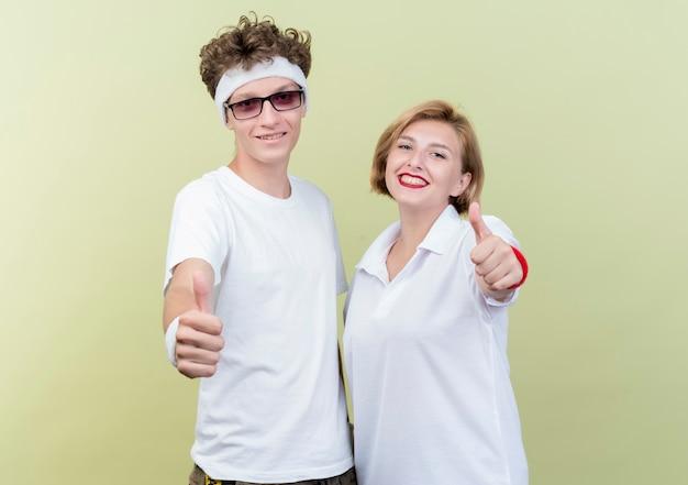 Молодая спортивная пара мужчина и женщина счастливы и позитивны, показывая пальцы вверх, стоя над светлой стеной