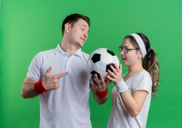 스포티 한 젊은 부부 남자와 여자는 녹색 벽 위에 축구 공을 들고 나란히 서