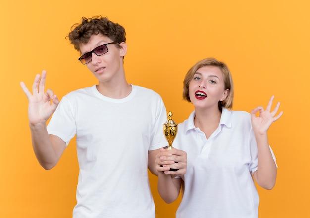 Молодая спортивная пара мужчина и женщина, стоящие вместе, держат трофей, показывая знак ок, улыбаясь, стоя над оранжевой стеной