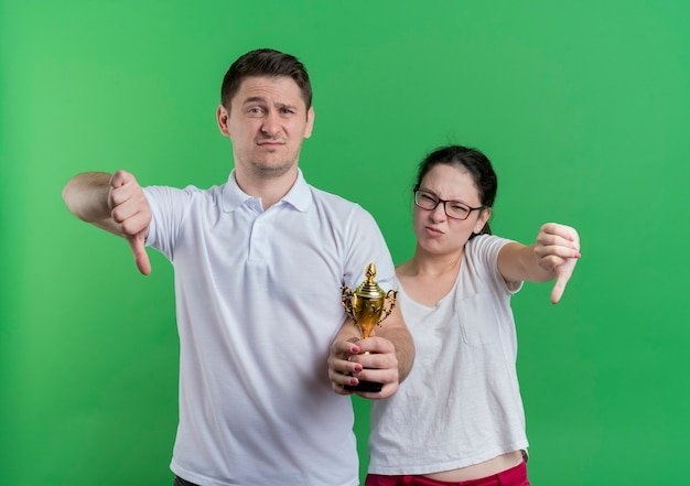 Молодая спортивная пара мужчина и женщина, стоящие вместе, держа трофей, показывая пальцы вниз, стоя над зеленой стеной