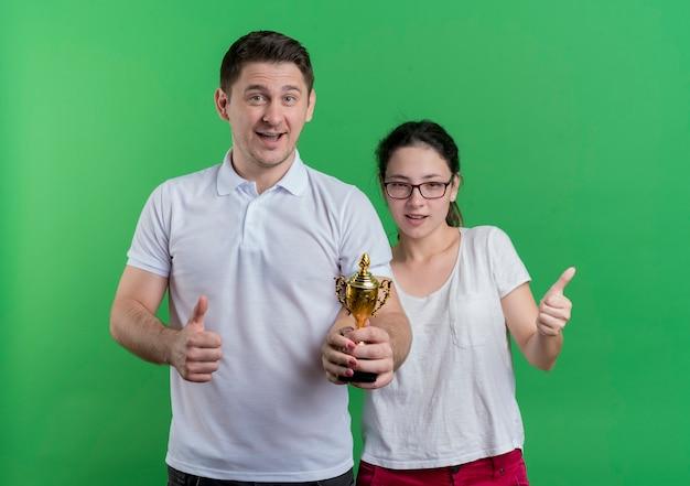 Молодая спортивная пара мужчина и женщина, стоящие вместе, держат трофей, показывая пальцы вверх, стоя над зеленой стеной