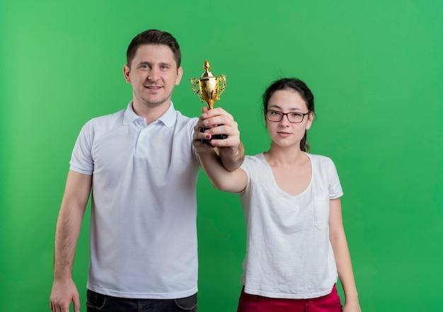 Молодая спортивная пара мужчина и женщина, стоящие вместе, держа трофей, улыбаясь, счастливые и уверенные, стоя над зеленой стеной