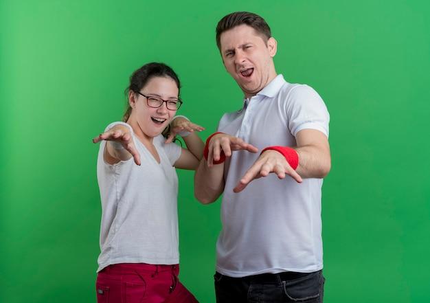 緑の壁の上に立って楽しんで笑顔で手を出して若いスポーティなカップルの男性と女性