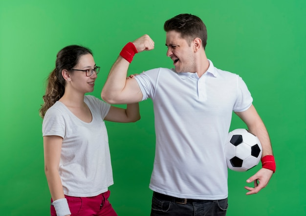 Young sporty couple man showing biceps holding soccer ball standing nex to his smiling girlfriend over green wall