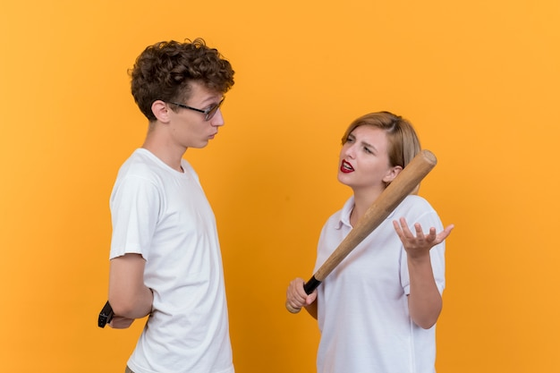 Young sporty couple man with a gun and skeptic woman with baseball bat looking at her boyfriend standing over orange wall