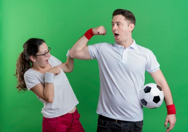 Uomo giovane coppia sportiva con pallone da calcio che mostra bicipite alla sua ragazza sorpresa in piedi sopra la parete verde