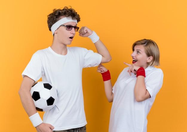 오렌지 벽 위에 서있는 그의 놀란 여자 친구에게 팔뚝을 보여주는 축구 공을 가진 젊은 스포티 한 부부 남자