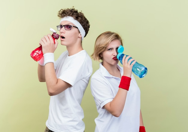 Young sporty couple man and woman drinking water after workout standing over light wall