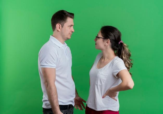 Giovane coppia sportiva uomo e donna che si guardano l'un l'altro discutendo in piedi sopra la parete verde