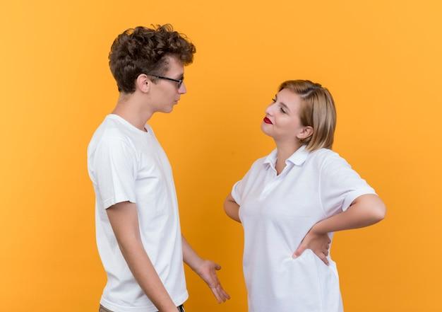 Giovane coppia sportiva uomo e donna che si guardano l'un l'altro discutendo in piedi sopra la parete arancione