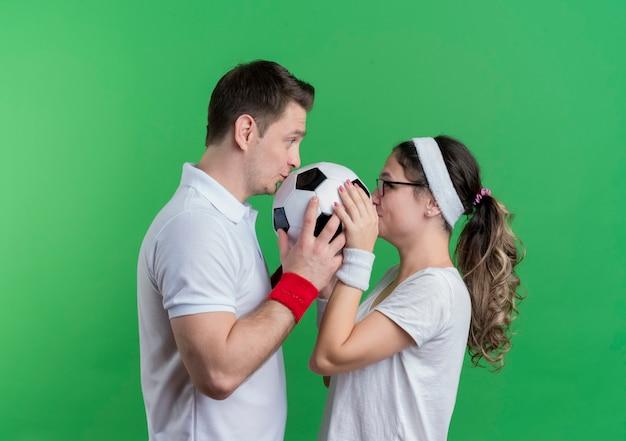 Giovane coppia sportiva uomo e donna in piedi faccia a faccia tenendo il pallone da calcio oltre la parete verde