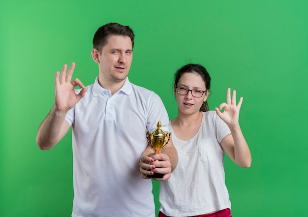 Young sporty couple man and woman standing together holding trophy  smiling showing ok signs standing over green wall