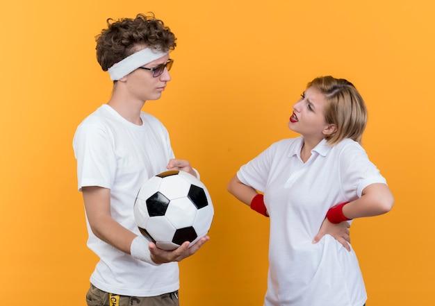 Giovane coppia sportiva uomo serio tenendo il pallone da calcio guardando la sua ragazza scontenta in piedi sopra la parete arancione